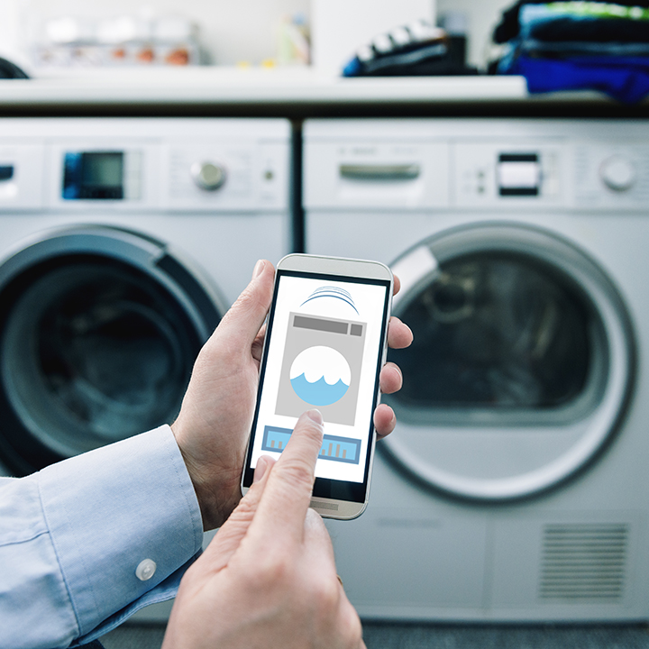 Man using smartphone to control washer and dryer.